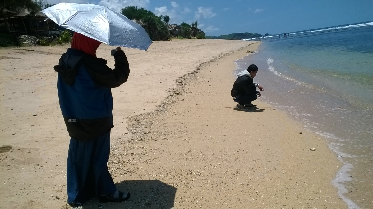 behind the scene foto-foto di pantai sepanjang. bawa payung segala